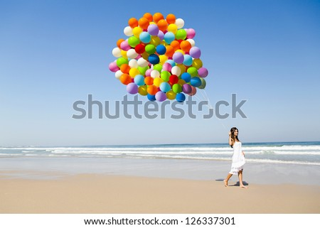 Beautiful girl walking in the beach holding dozens of colored balloons - stock photo