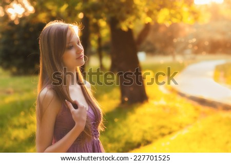 Beautiful girl walking in the nature on sunny summer day. - stock photo