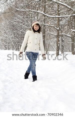 Beautiful girl walking in winter forest - stock photo