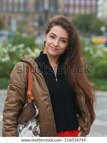 Beautiful girl walking on the city street with happy smile - stock photo