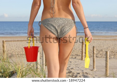 Beautiful girl walking to the beach with plastic bucket and spade