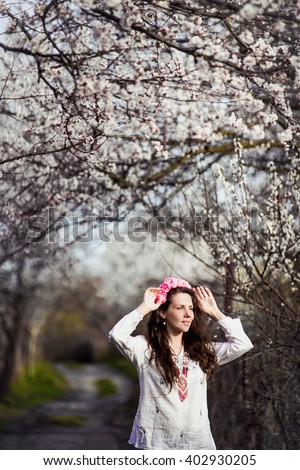 beautiful girl walks in the lush garden dressed in a wreath. Spring - stock photo