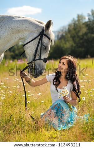 Beautiful girl walks on white horse on a summer meadow - stock photo