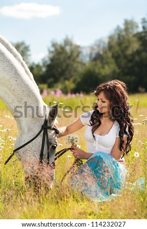 Beautiful girl walks on white horse on a summer meadow