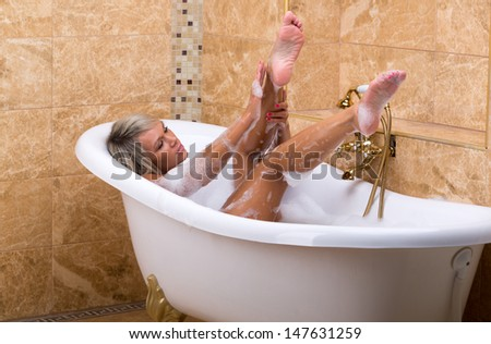 Beautiful girl washes in a luxurious bubble bath - stock photo