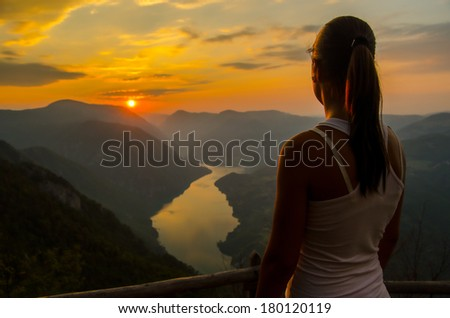 Beautiful girl watching river and hills from the top of the mountain in summer. - stock photo