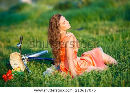 Beautiful girl wearing a nice white dress having fun in park with bicycle. Healthy outdoor lifestyle concept. Vintage scenery. Pretty girl with retro look with bike and basket with flowers - stock photo