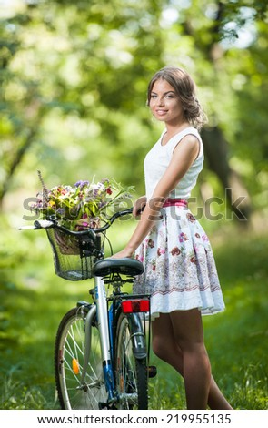 Beautiful girl wearing a nice white dress having fun in park with bicycle. Healthy outdoor lifestyle concept. Vintage scenery. Pretty blonde girl with retro look with bike and basket with flowers - stock photo
