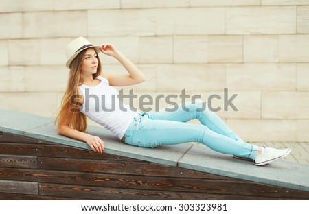 Beautiful girl wearing a summer straw hat and jeans enjoying in the city