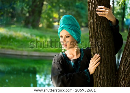 Beautiful girl wearing a turban and a stylized ethnic costume in the summer park