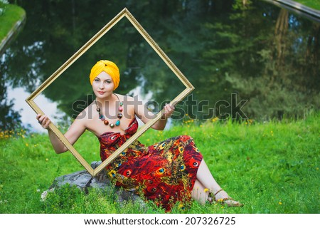 Beautiful girl wearing a turban and a stylized ethnic costume near Gothic church