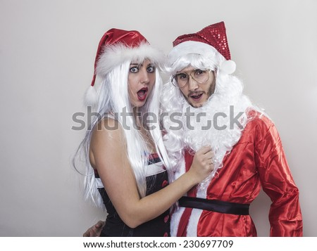 Beautiful girl wearing Christmas hat unmasking Santa Claus
