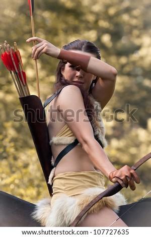 Beautiful girl wearing clothes in amazon style on horseback - stock photo