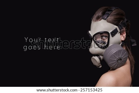 Beautiful girl wearing gas mask and looking card - stock photo