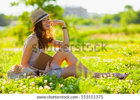 beautiful girl wearing hat with book sitting on grass - stock photo