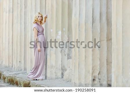 beautiful girl  wearing long dress near the columns - stock photo