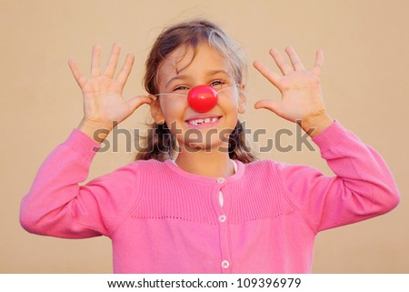 Beautiful girl wearing pink blouse with red clown nose smiles and teases. - stock photo