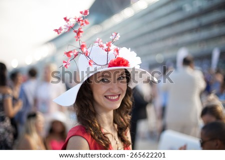 Beautiful girl wearing Sakura flower hat smiling at the Dubai World Cup Horse Race  - stock photo