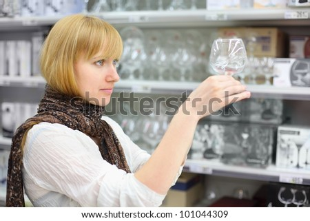Beautiful girl wearing scarf looks at glass in shop; shallow depth of field - stock photo