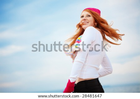 Beautiful girl wearing winter clothing over sky - stock photo