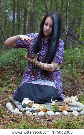 Beautiful girl witch prepares witchcraft the drug in the woods   - stock photo