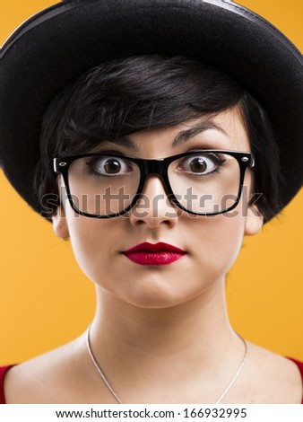 Beautiful girl with a astonished expression, wearing a hat and nerd glasses over a yellow background - stock photo