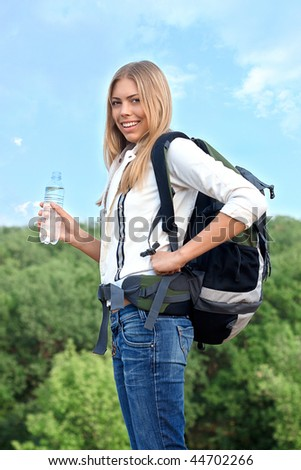 Beautiful girl with a backpack and bottle of water is smiling