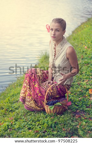 Beautiful girl with a basket of grapes near the river, shooting in the park - stock photo