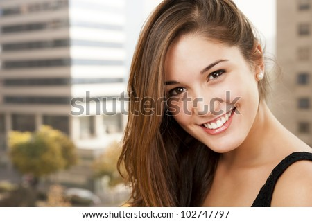Beautiful girl with a beautiful face is smiling at the lens.