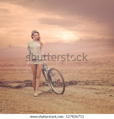 beautiful girl with a bicycle at sunset - stock photo