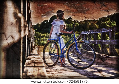 Beautiful girl with a bicycle on the bridge. Photos in the grunge style. - stock photo