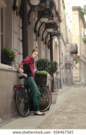 beautiful girl with a bicycle on the streets of the beautiful city - stock photo