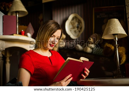 Beautiful girl with a book in cafe - stock photo