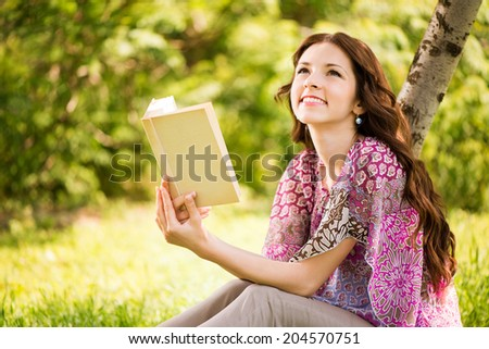 Beautiful Girl with a book in the park sitting on the grass and Expressing Positivity. - stock photo