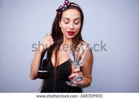 beautiful girl with a bottle of champagne with glasses - stock photo