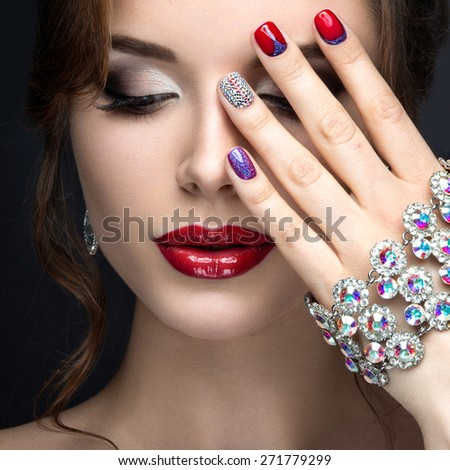 Beautiful girl with a bright evening make-up and red manicure with rhinestones. Nail design. Beauty face. Picture taken in the studio on a black background.