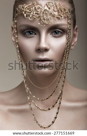 Beautiful girl with a bronze skin, pale makeup and unusual accessories. Art beauty image. Beauty face. Picture taken in the studio.