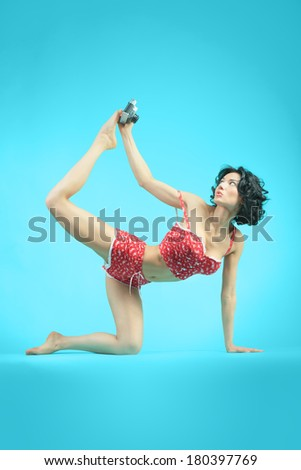 beautiful girl with a camera in pajamas demonstrates yoga - stock photo