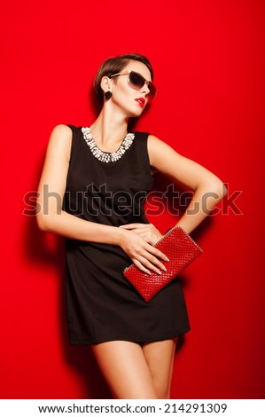 Beautiful girl with a  clutch bag and sunglasses in her hands - stock photo