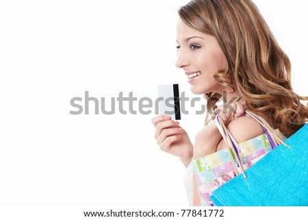 Beautiful girl with a credit card and shopping bags on white background - stock photo
