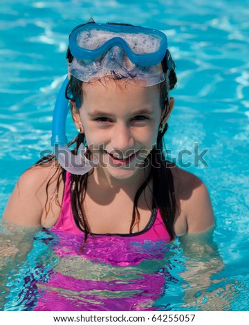 Beautiful girl with a diving mask and a snorkel smiling in a pool