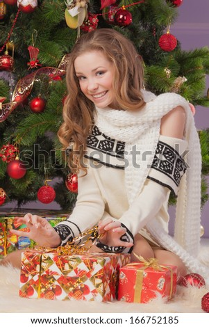 Beautiful girl with a gift near the Christmas tree