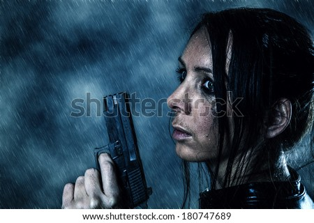 Beautiful girl with a gun in the rain - stock photo