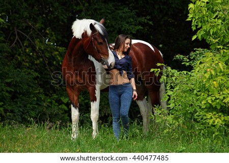 Beautiful girl with a horse in woodland
