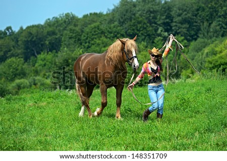 Beautiful girl with a horse on a farm