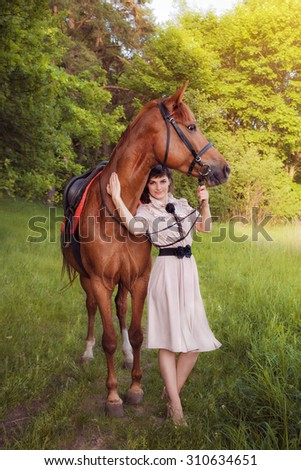 Beautiful girl with a horse walking in the woods in the summer