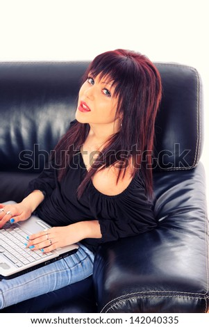 Beautiful  girl with a laptop computer sitting on the couch