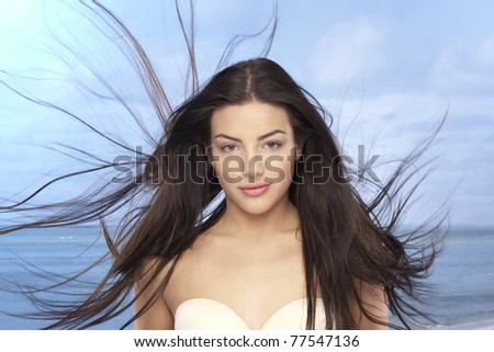 Beautiful girl with a long hair on the beach - stock photo