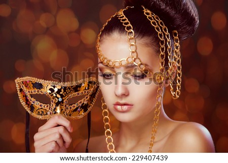 Beautiful girl with a masquerade mask in hands - stock photo