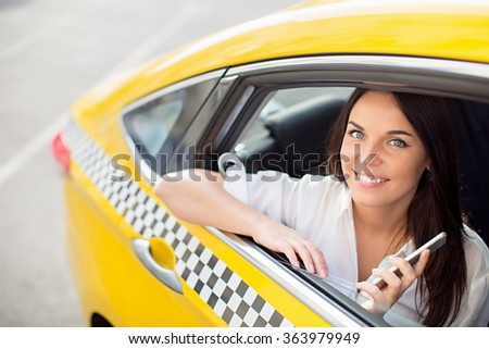 Beautiful girl with a phone in a taxi - stock photo